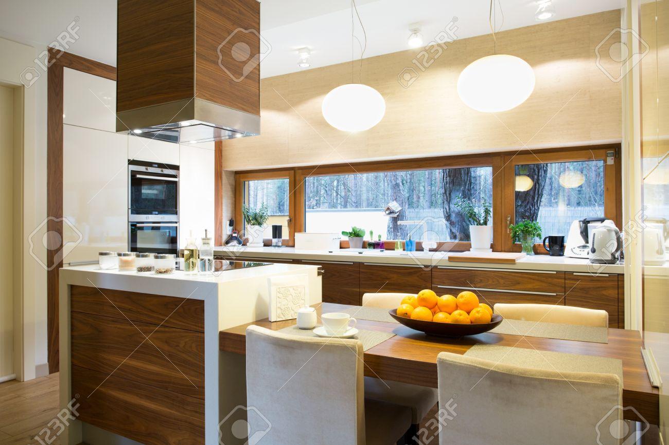cocina de madera brillante moderna con isla y mesa grande foto de archivo