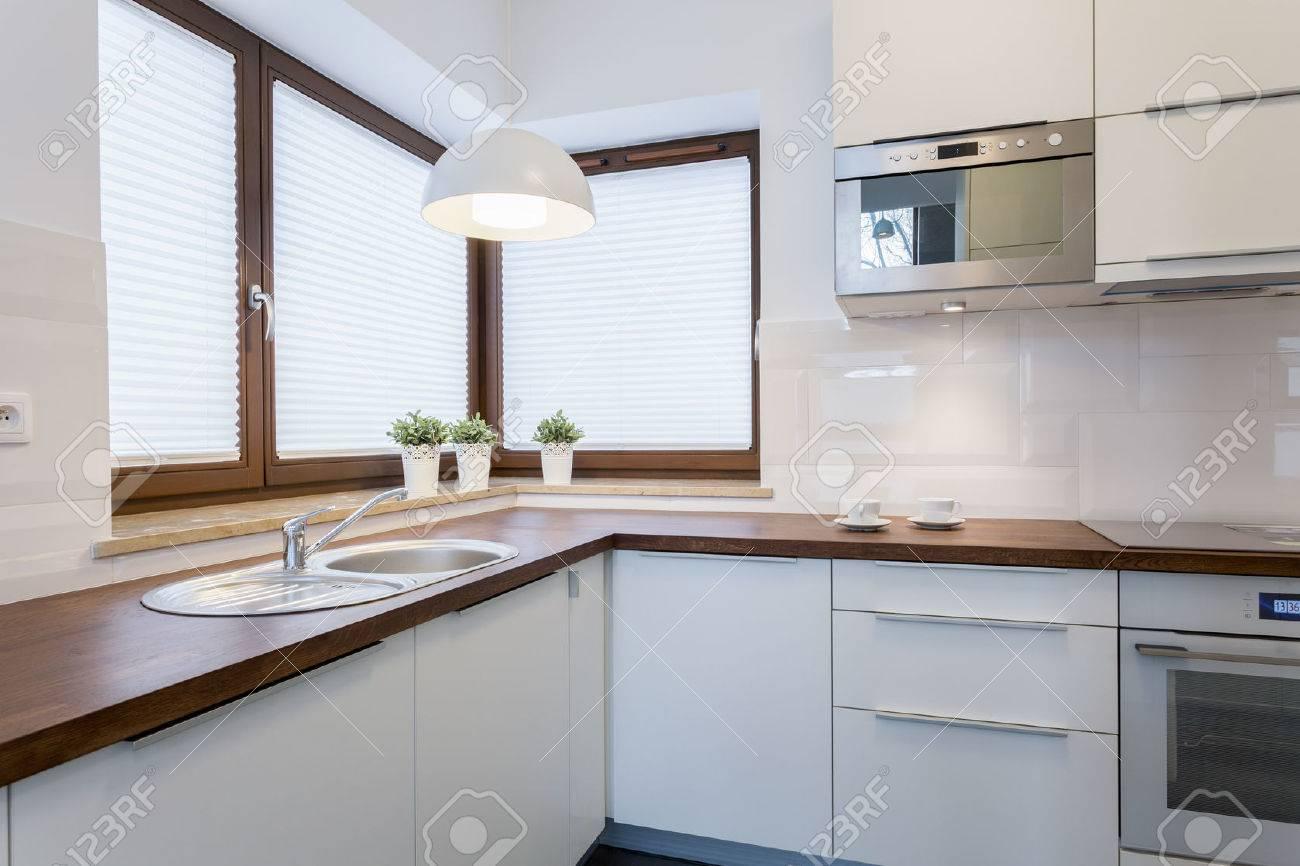 encimeras de madera y armarios blancos en la cocina tradicional foto de archivo