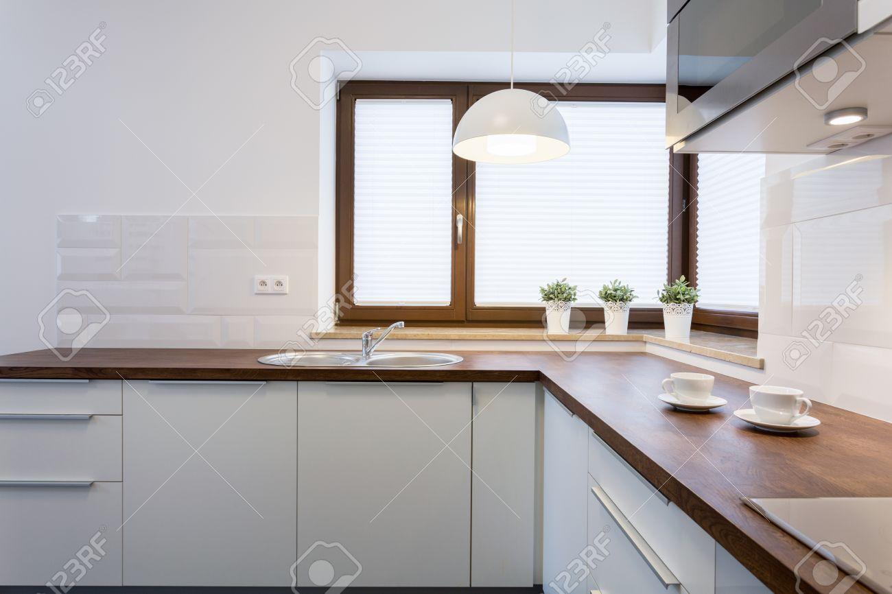 encimeras de madera y armarios blancos en la cocina de lujo foto de archivo