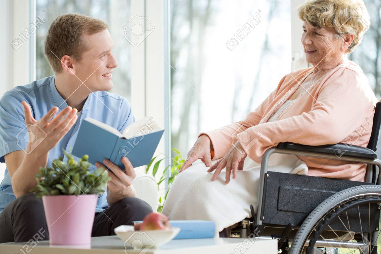 Male care assistant reading senior woman book - 38199425
