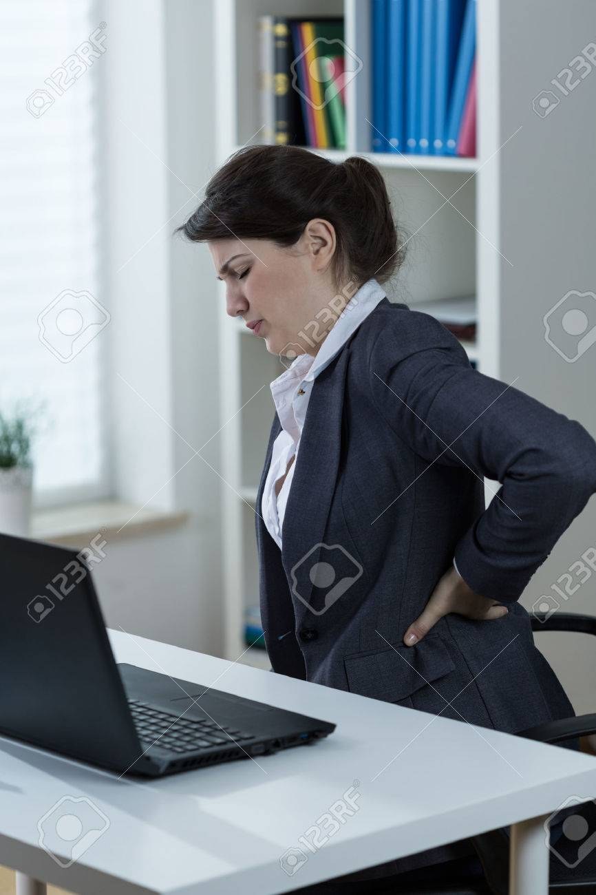 office worker having backache caused by sedentary work stock photo
