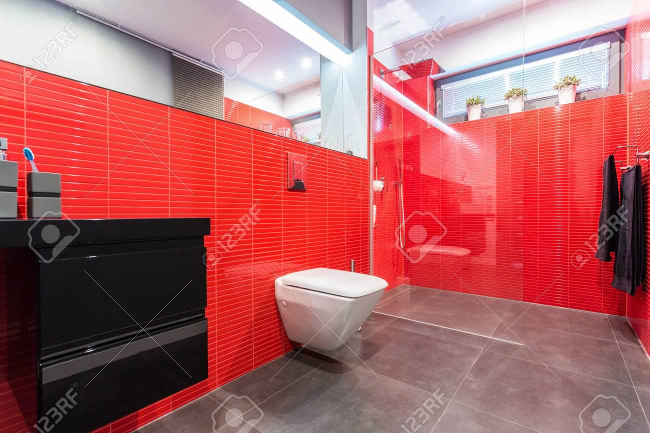 cuarto de bao moderno con azulejos rojos con aseo y cabina foto de archivo