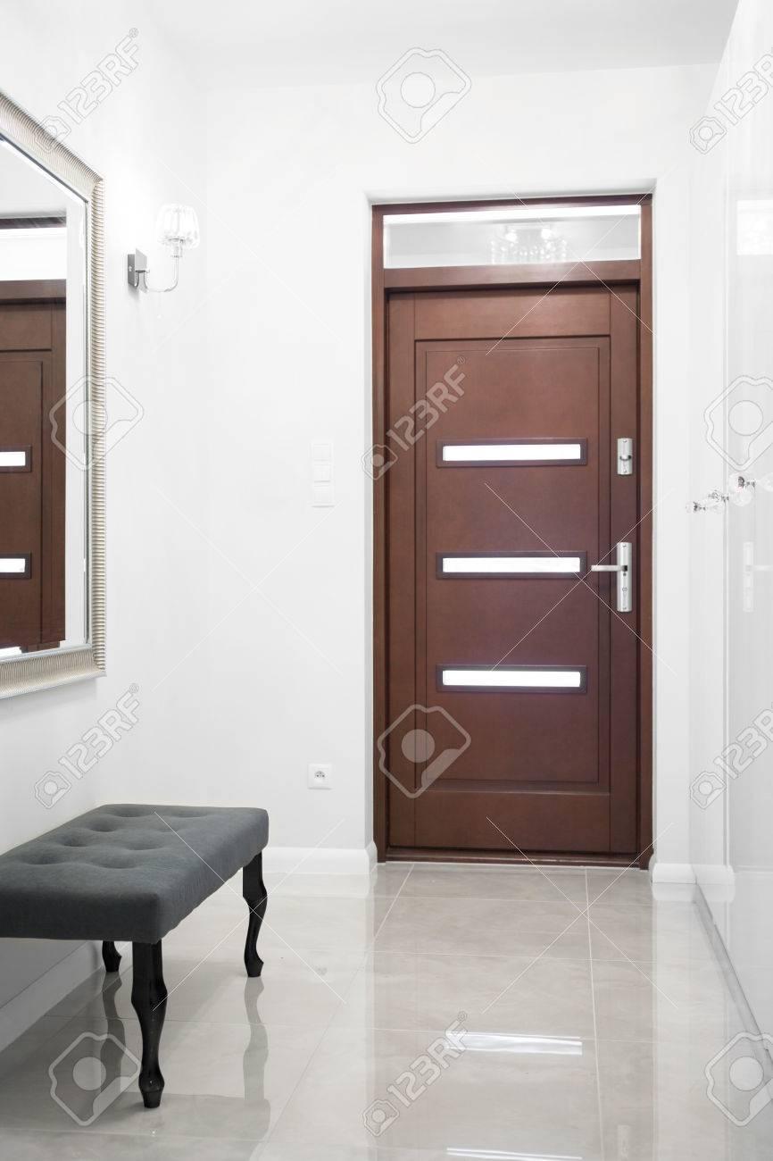 Photo de la porte d\'entrée en bois dans le grand couloir blanc