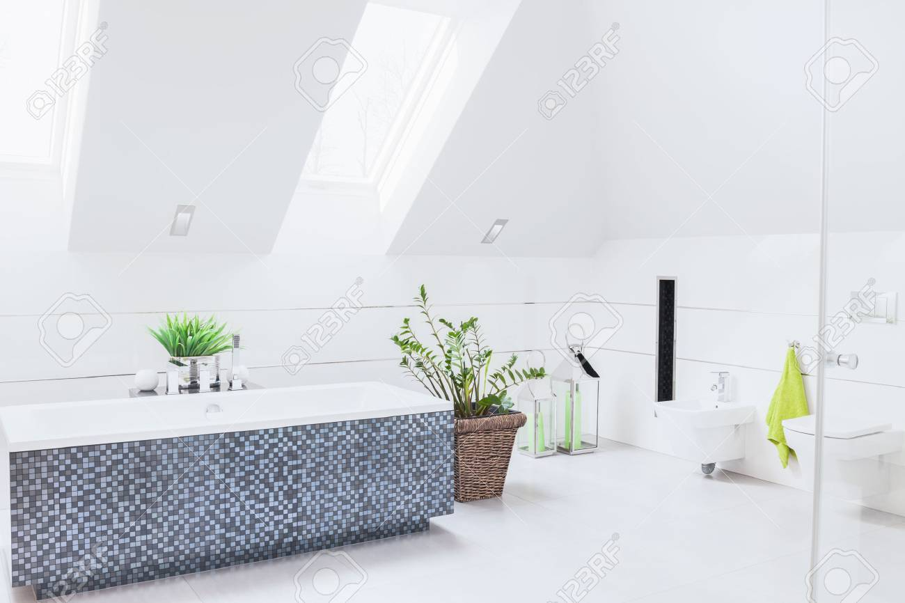 Salle de bain blanc spacieuse avec grande baignoire en mosaïque