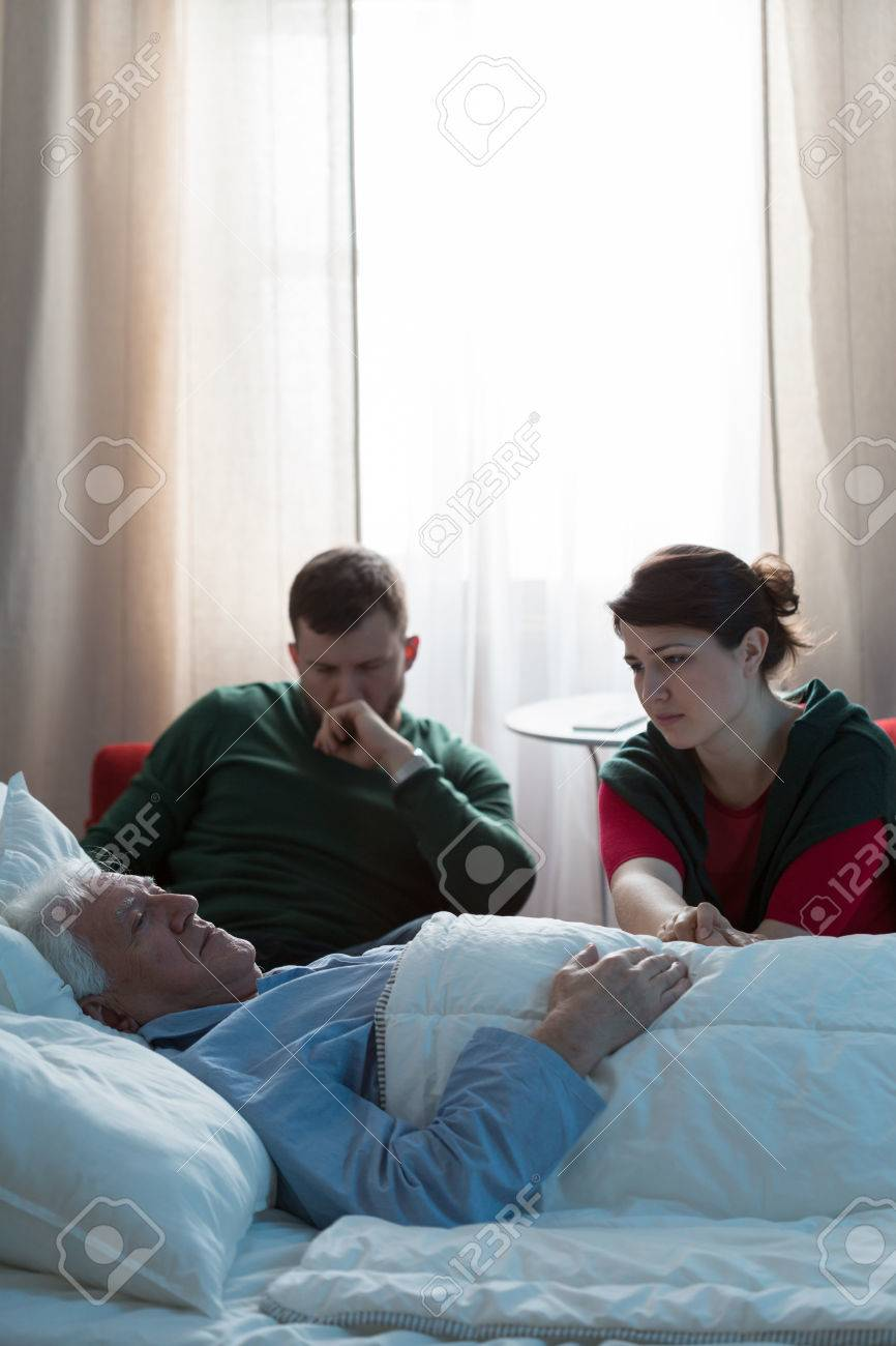 Two worried adult kids watching their terminally ill dad