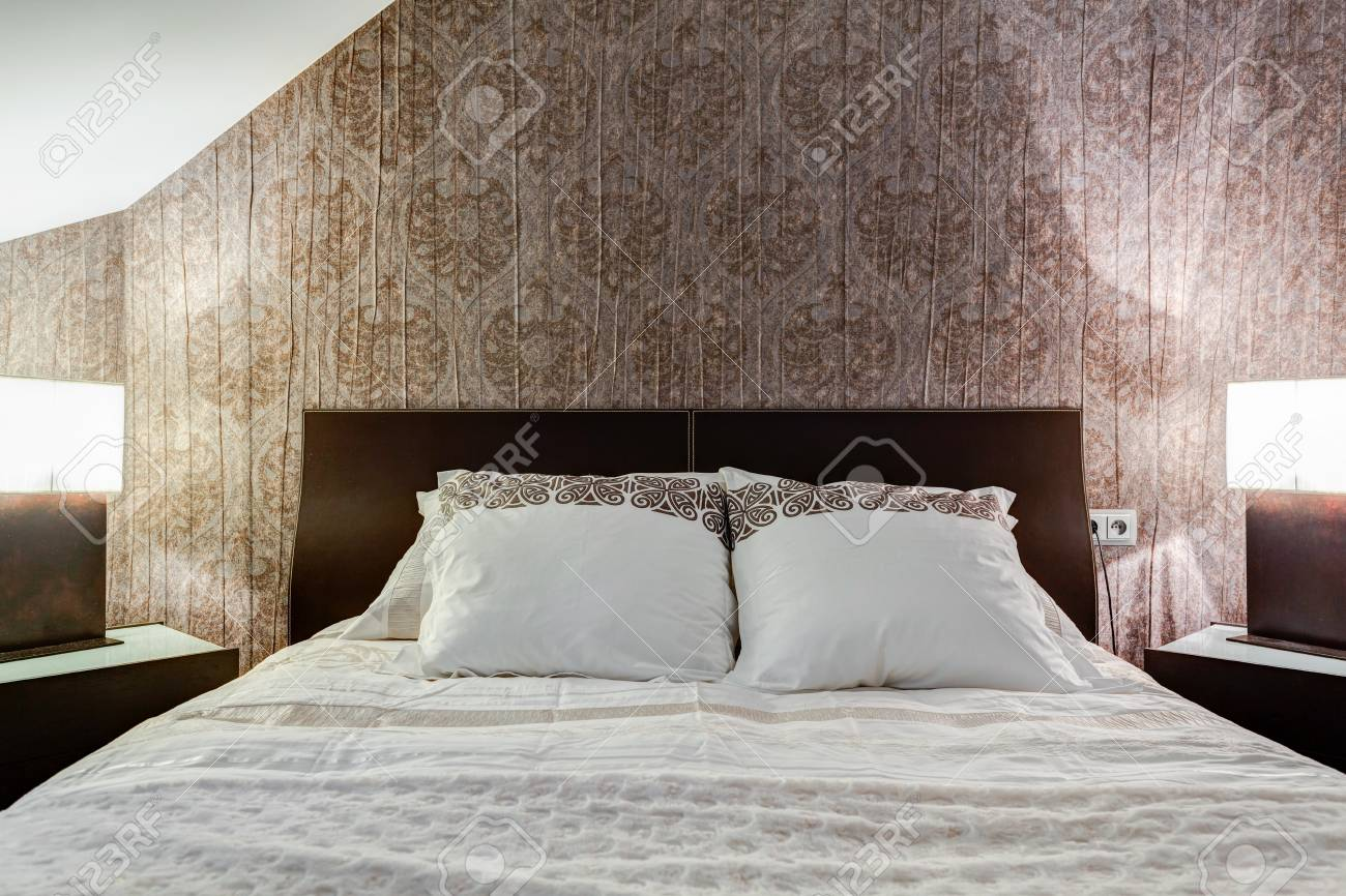 Comfortable Bed And Brown Wallpaper In Elegant Bedroom Stock Photo    42093570