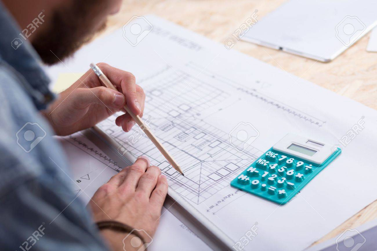 Architect with blueprint and calculator estimating project cost architect with blueprint and calculator estimating project cost stock photo 44240859 malvernweather Images