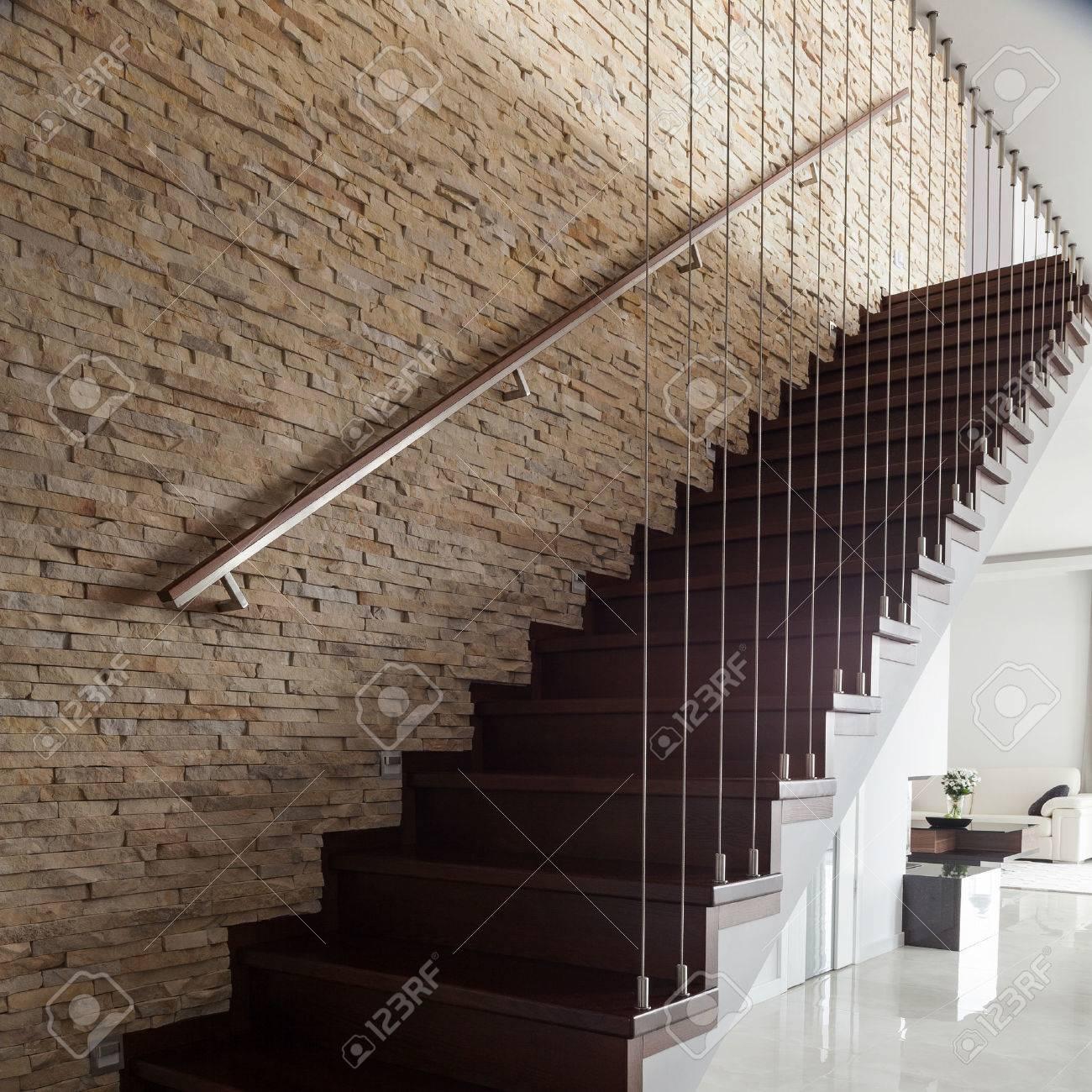 Mur de brique et escaliers en bois en intérieur conçu