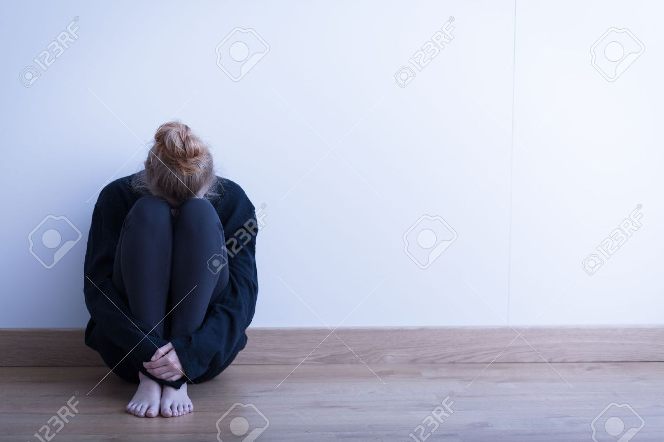 Image of a woman siiting curled up on the ground - 45531310