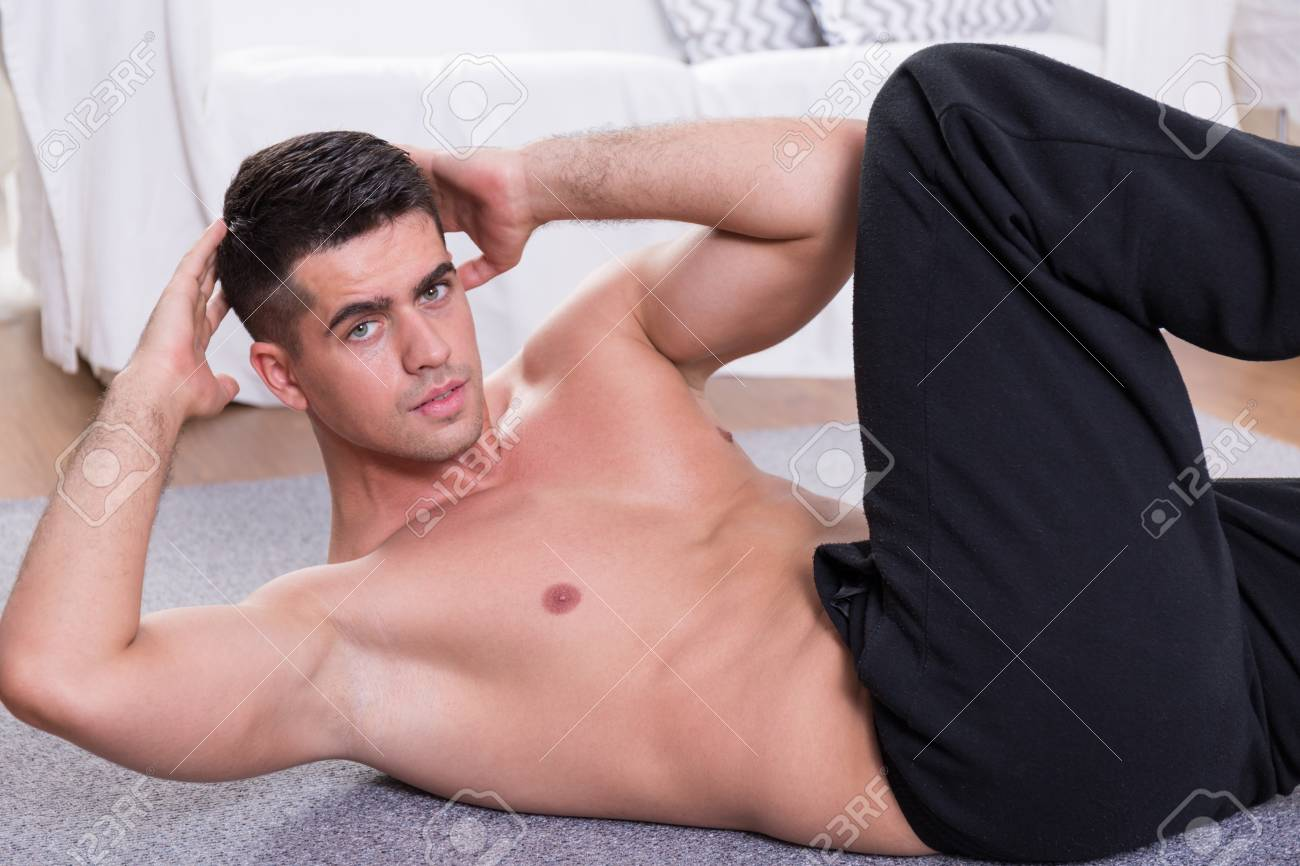 Sporty Man Doing Oblique Crunches On The Floor Stock Photo