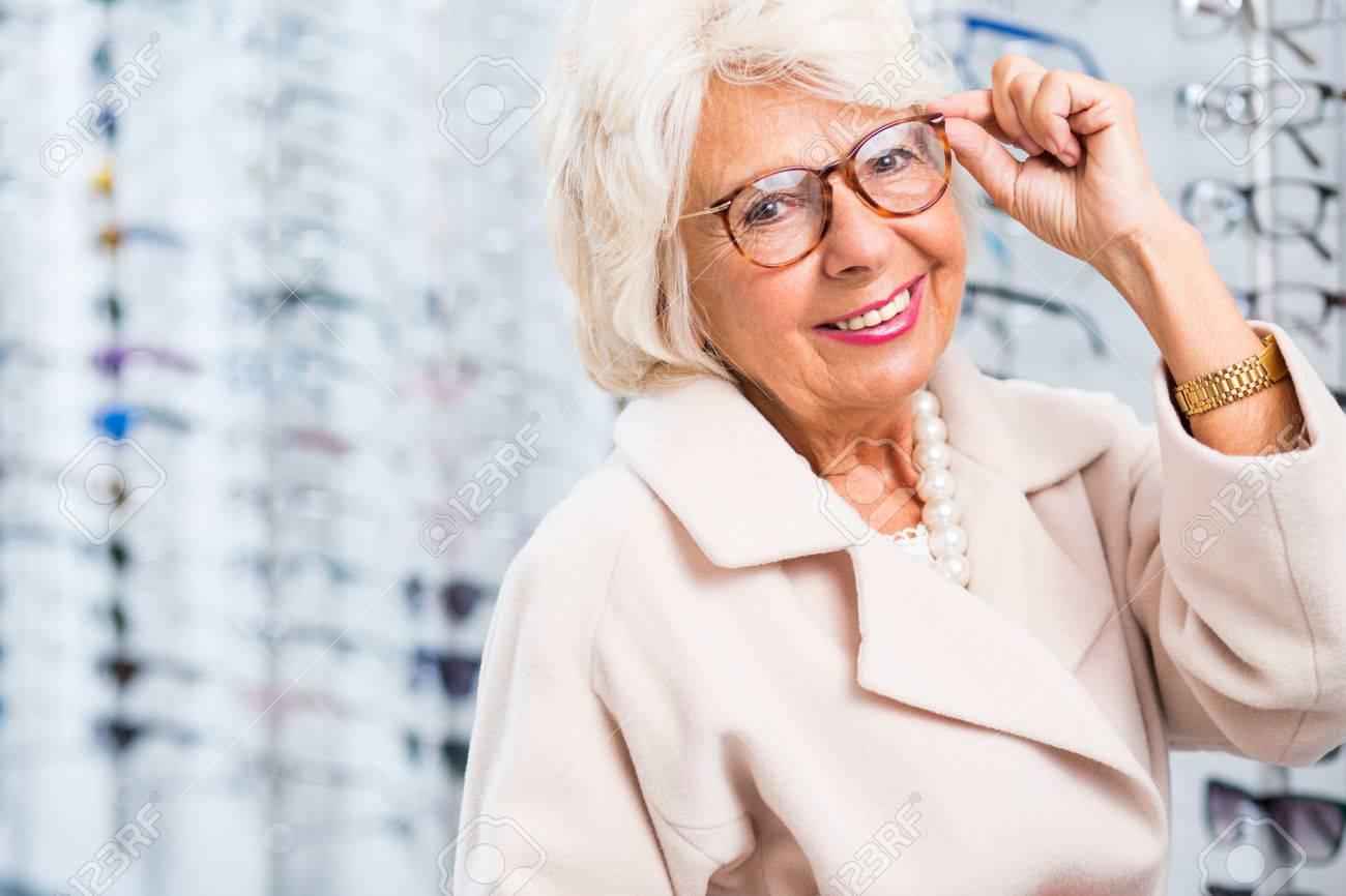 Elderly woman choosing reading glasses in optical shop - 47230130