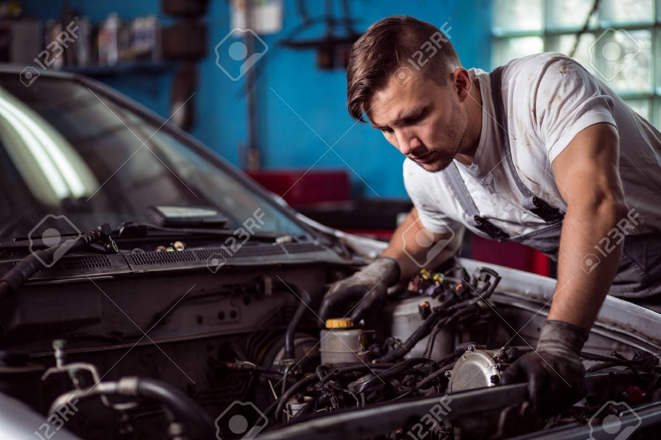 Male Mechanic Is Looking At Parts Inside Car Bonnet Stock Photo