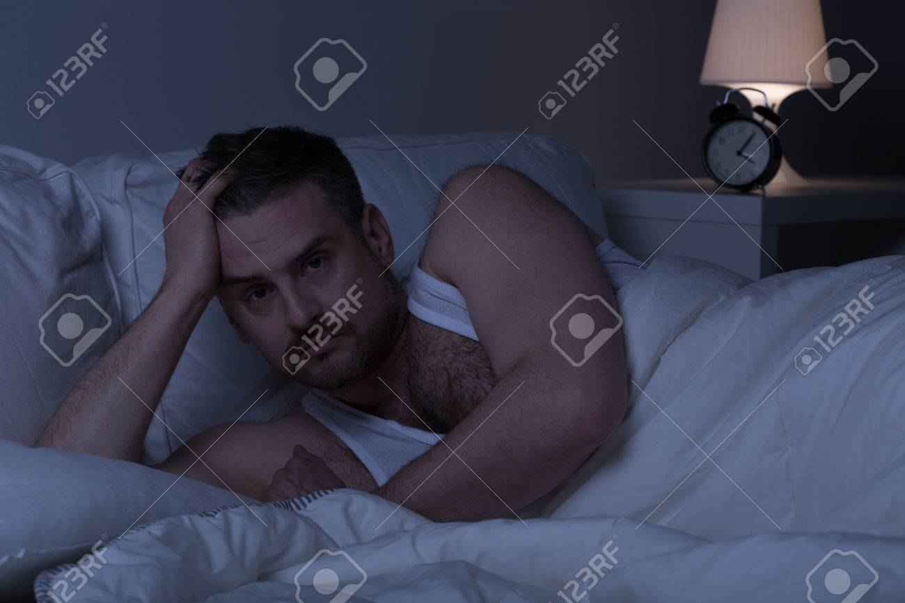 tired slepless man staying awake in bed stock photo picture and stock photo tired slepless man staying awake in bed