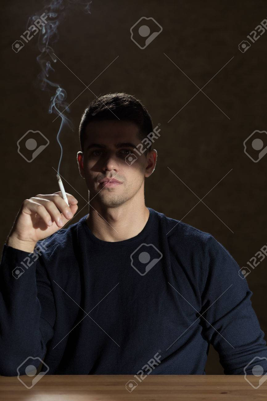 Stock photo young man is smoking a cigarette alone