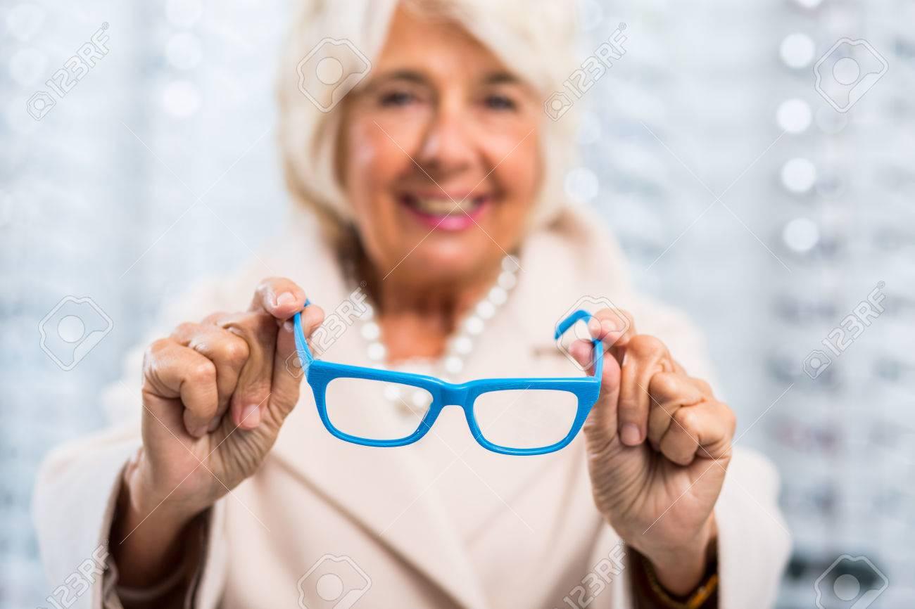 Photo Of Content Senior Woman Holding Modern Blue Frames Stock Photo ...