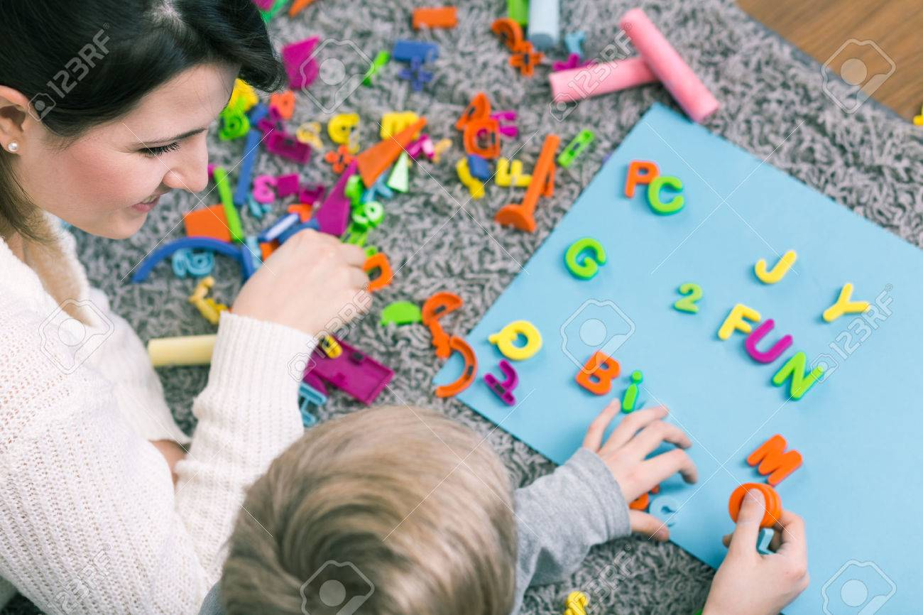 Boy during session with speech therapist learning letters - 51794112