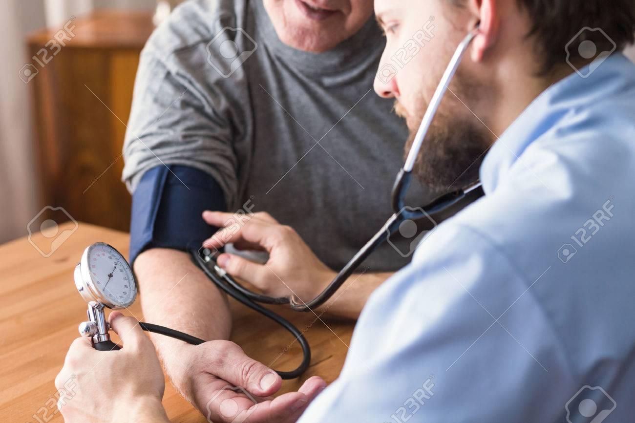Hypertensive senior man during blood pressure measurement - 51795180