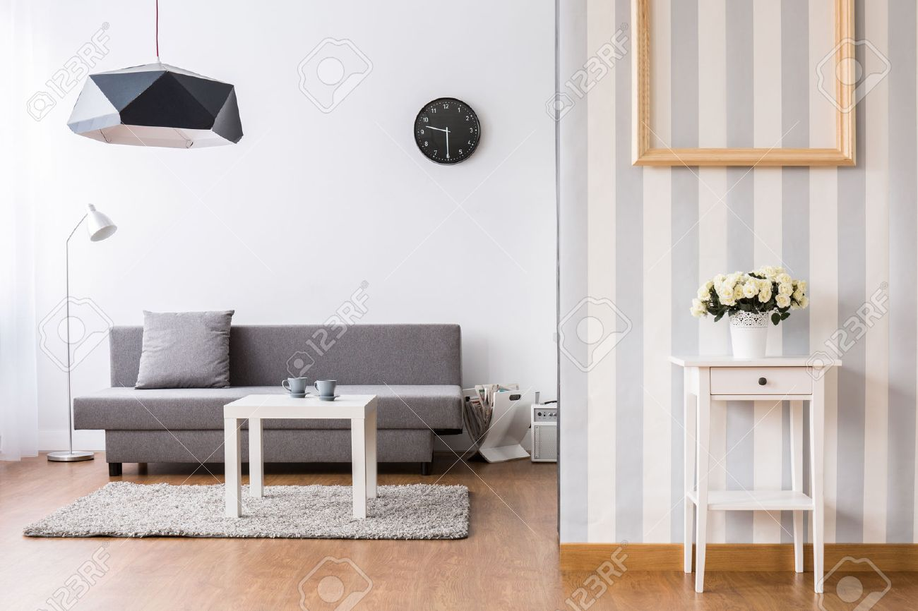 Stilvolle Wohnzimmer Mit Grauem Sofa Und Kleinen Couchtisch. Leichte  Zwischen Mit Böden Und Dekorative Tapeten