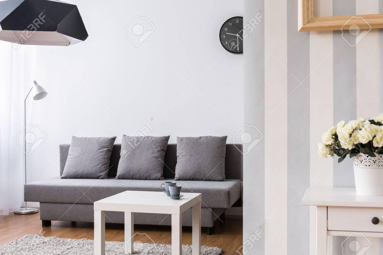 Salon moderne avec grand canapé gris et petite table basse. intérieur clair  avec du papier peint décoratif.