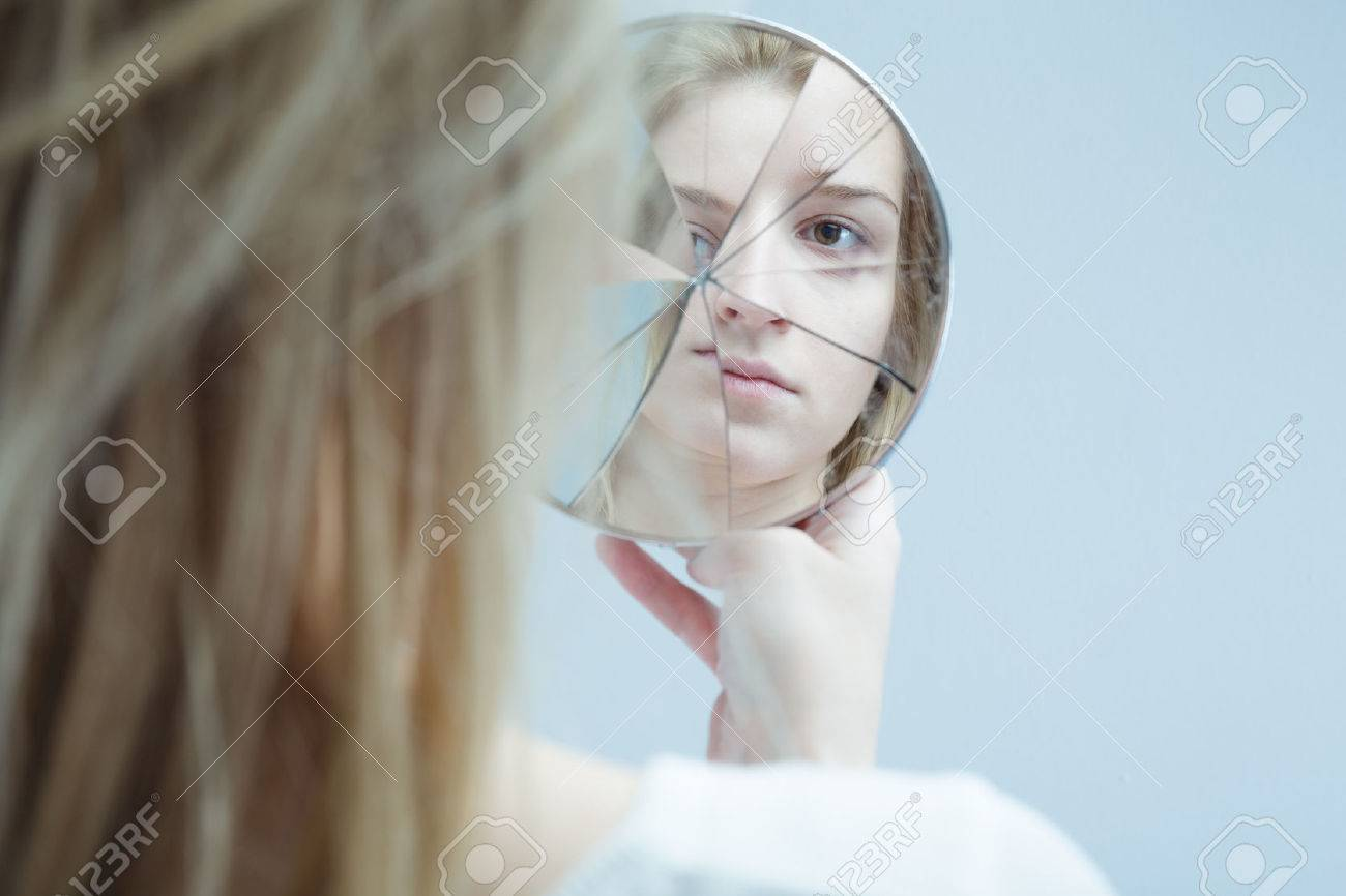 Image of woman with mental disorder holding broken mirror - 52545484