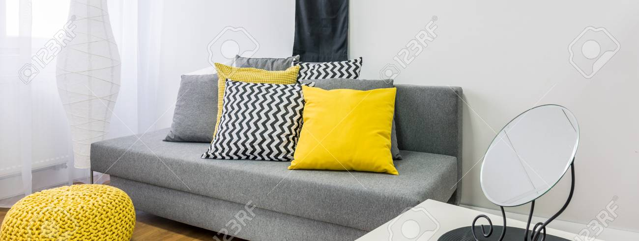 Close Up Of Grey Sofa With Decor Cushions In Black Yellow Grey