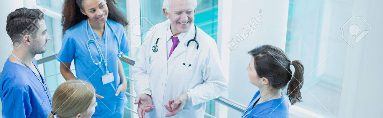 Elderly wise professor talking with his young students on medical internship - 54024140