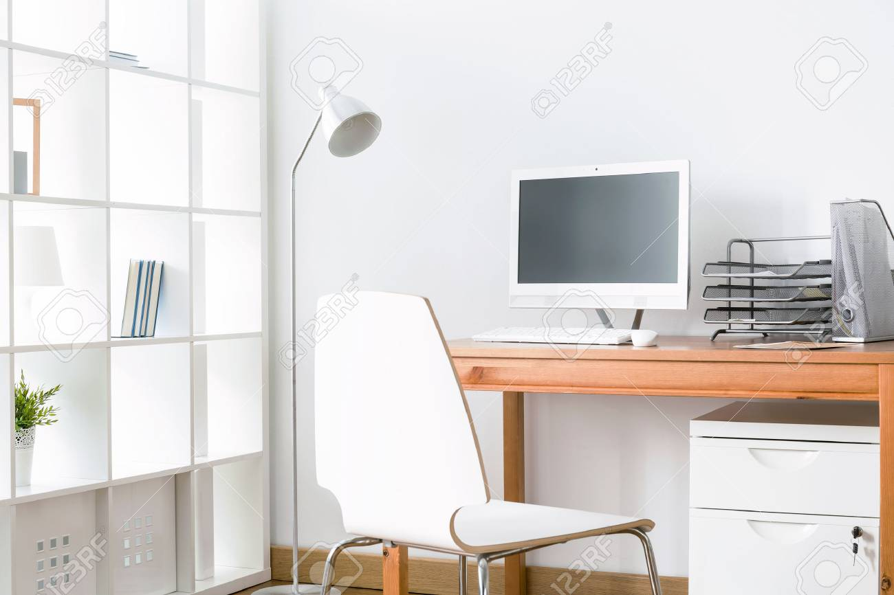 Light home office with simple wood desk, chair, computer and..
