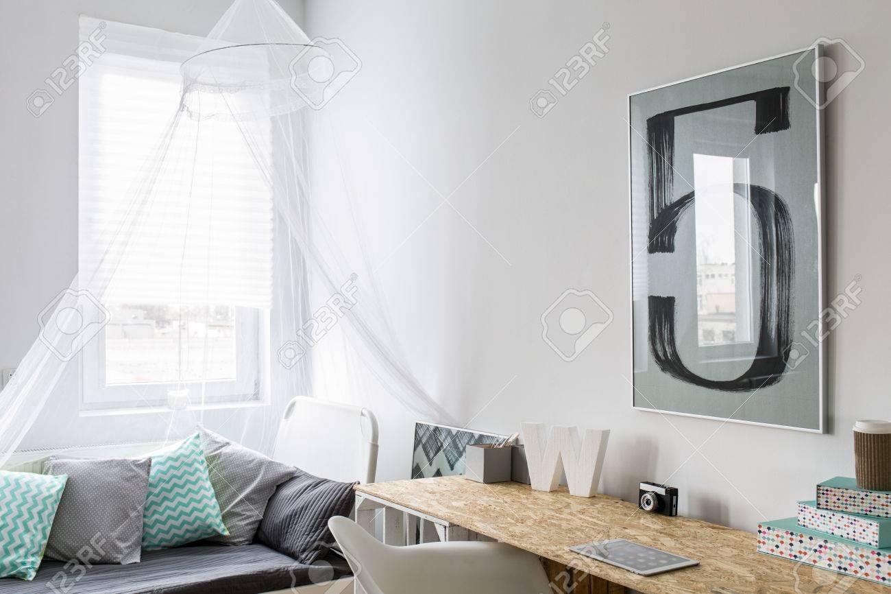 Chambre moderne et élégante avec lit à baldaquin et de couleur oreillers. À  côté de lui un bureau bien rangé bois