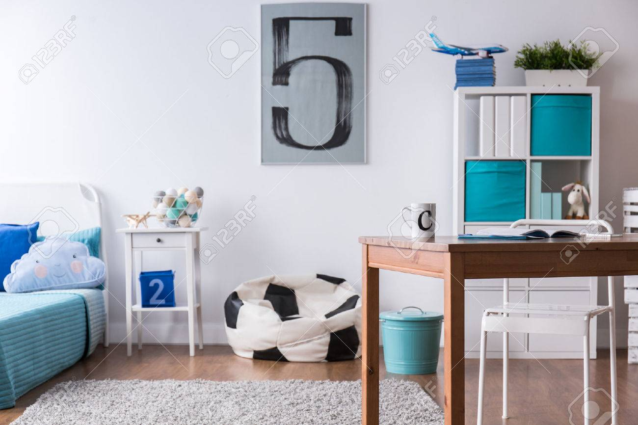 La chambre de garçon élégant avec un bureau en bois et un oreiller