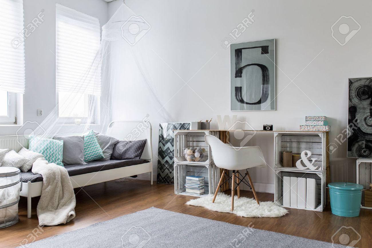 Gemütliche Hipster Schlafzimmer Mit Holzfußboden Und Original Schreibtisch.  Weiß Bett Mit Farbe Kissen Und Baldachin