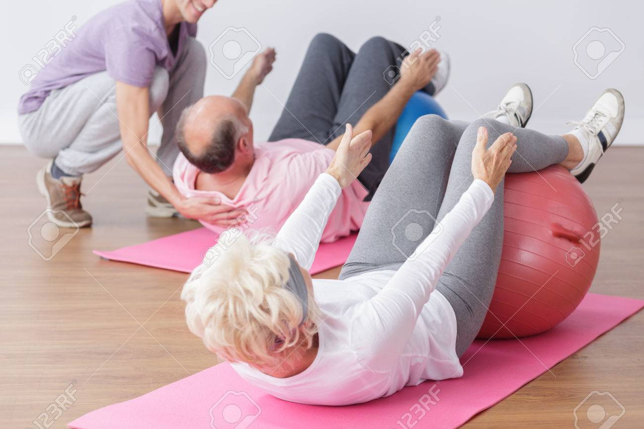 Senior exercising on gym ball with professional instructor. - 54417213