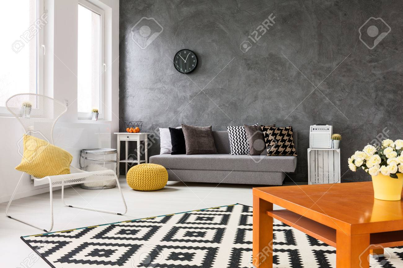 . Grey living room with sofa  chair  small wood table yellow details