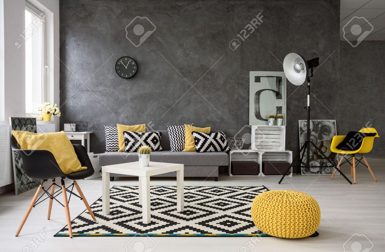 Spacieux, salon gris avec un canapé, des chaises, une lampe sur pied,  petite table basse, décorations en jaune, noir et blanc
