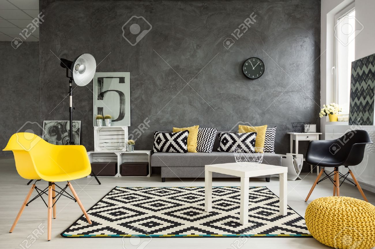 Grey living room with sofa, chairs, standing lamp, small table,..