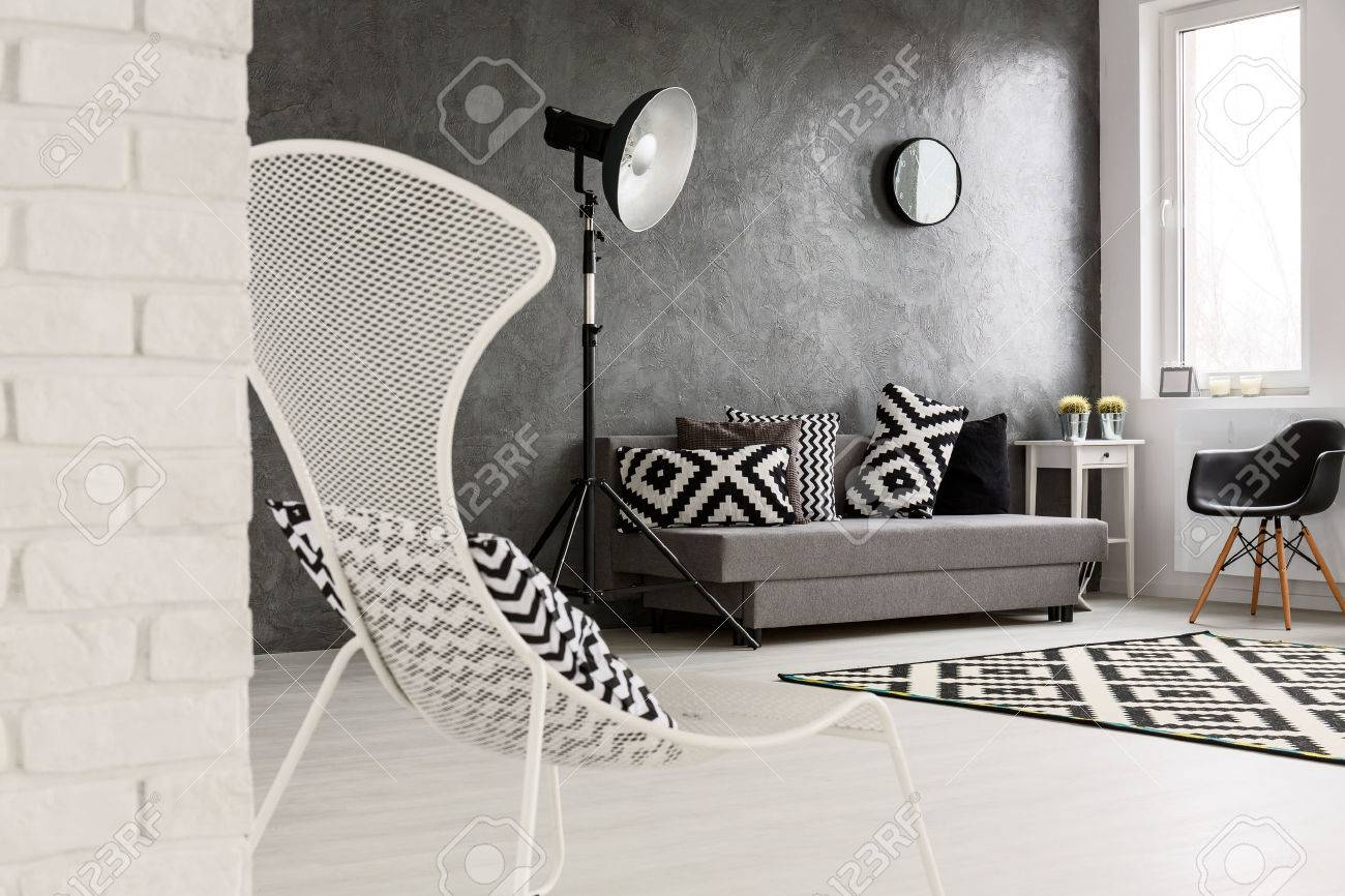 Grey Living Room With Sofa Chairs Standing Lamp Brick Wall And Decorations In