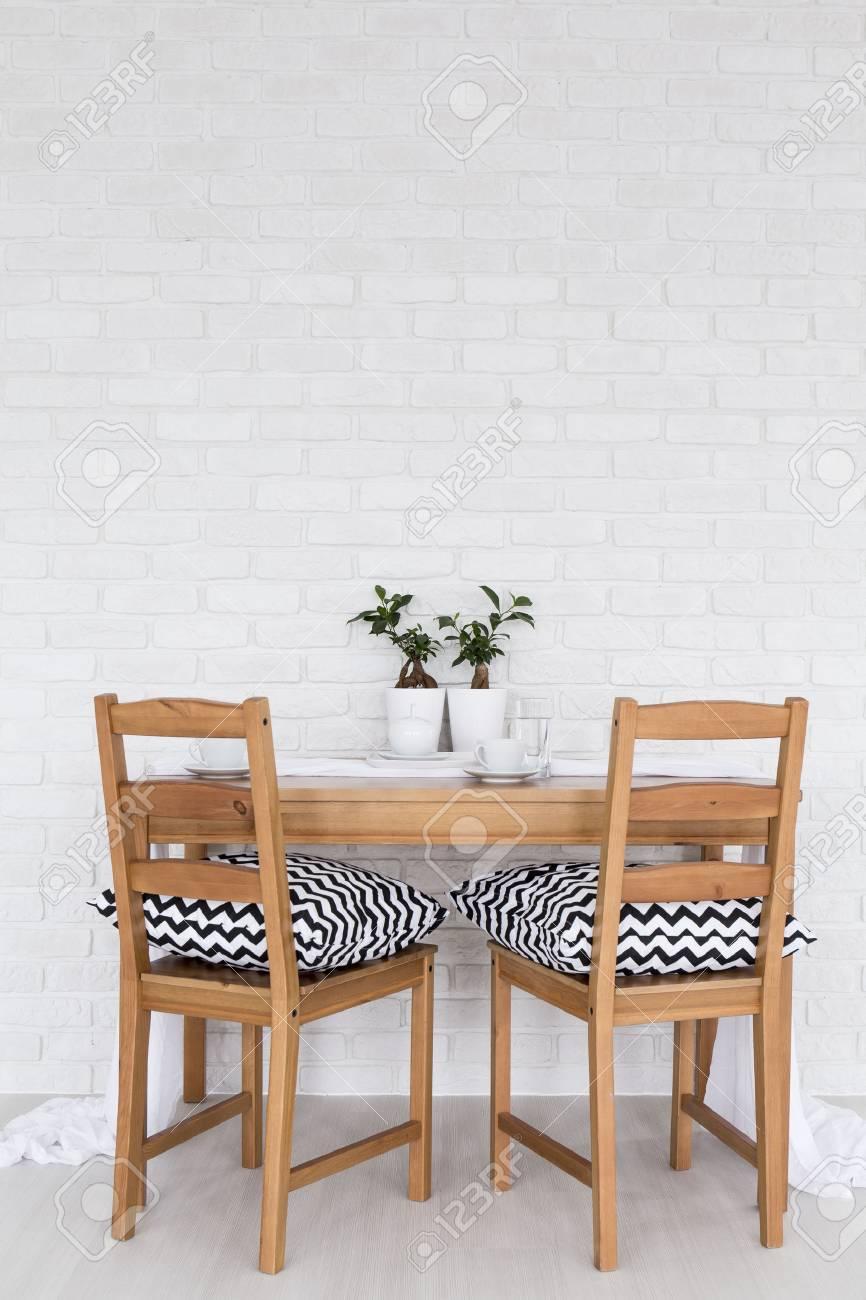 eenvoudige houten tafel en twee stoelen staan in het licht interieur met decoratieve bakstenen