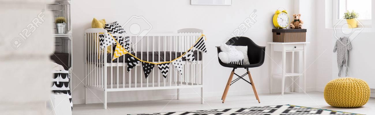 Espaciosa, Cuarto De Bebé Con Cuna Luz Blanca, Negro Silla Y ...