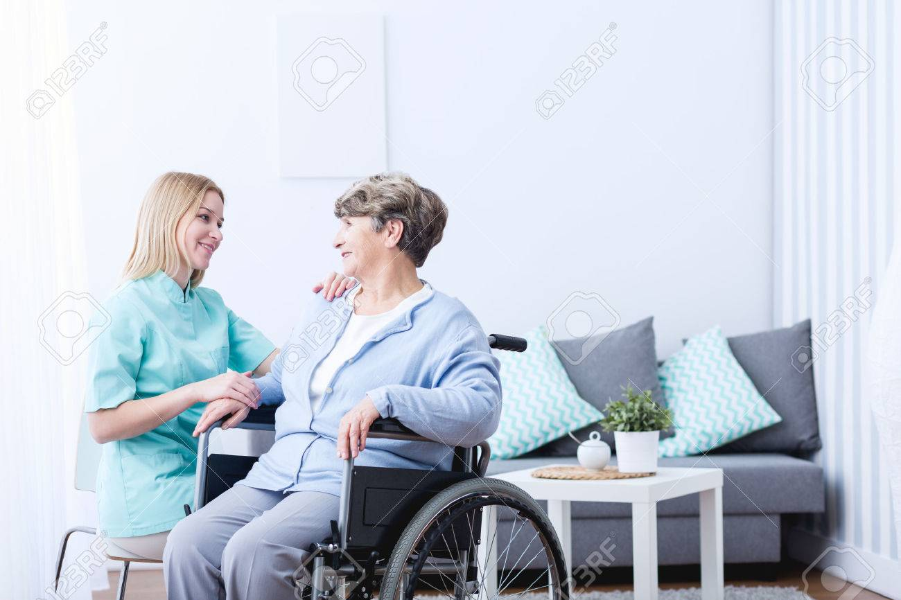 Photo of senior lady on wheelchair and her caregiver - 54785007