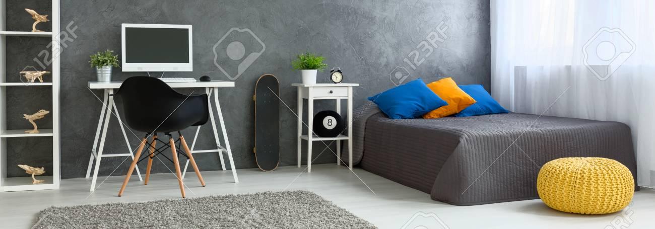 Panorama d\'une chambre à coucher moderne agencée en gris, avec un mobilier  simple, une planche à roulettes et des avions de modèle