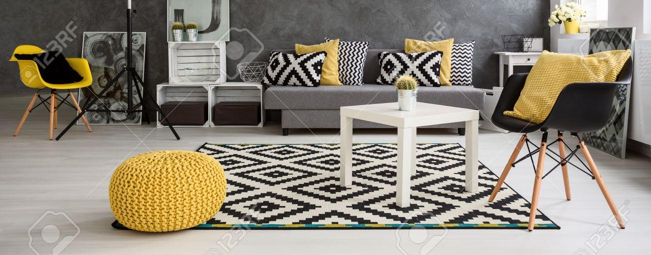 Panorama d\'un spacieux salon moderne agencée dans le style scandinave,  meublé en gris et blanc avec des éléments jaunes