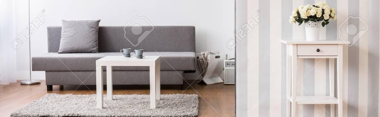 Nuovo elegante soggiorno dal design moderno con divano grigio e tavolino in  legno
