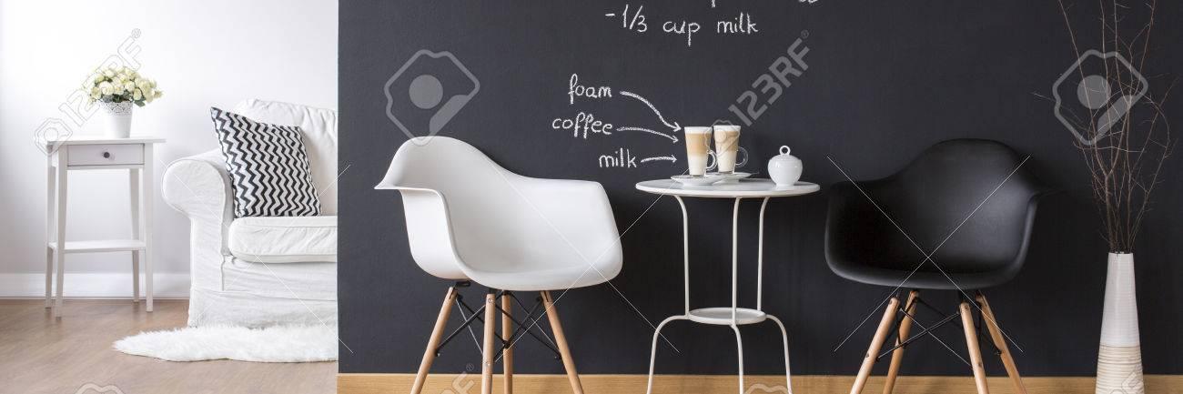 Intérieur moderne en noir et blanc avec une petite table, deux chaises et  un canapé