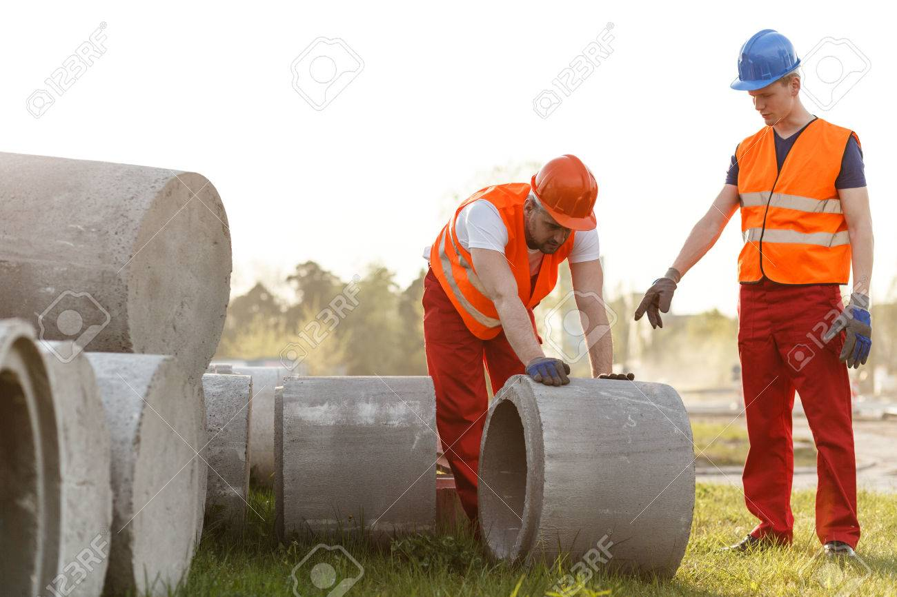 image of hard working road builder with cement pipe stock photo