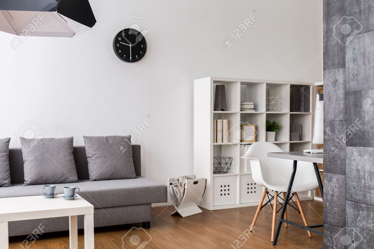 Modern,minimalist living room with resting space, racks and desk..