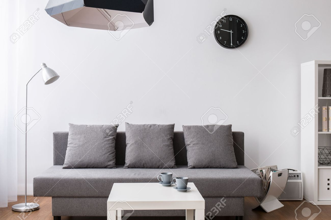 Modern Minimalist Living Room Furnished In Grey And White With Designer Lamps Stock Photo