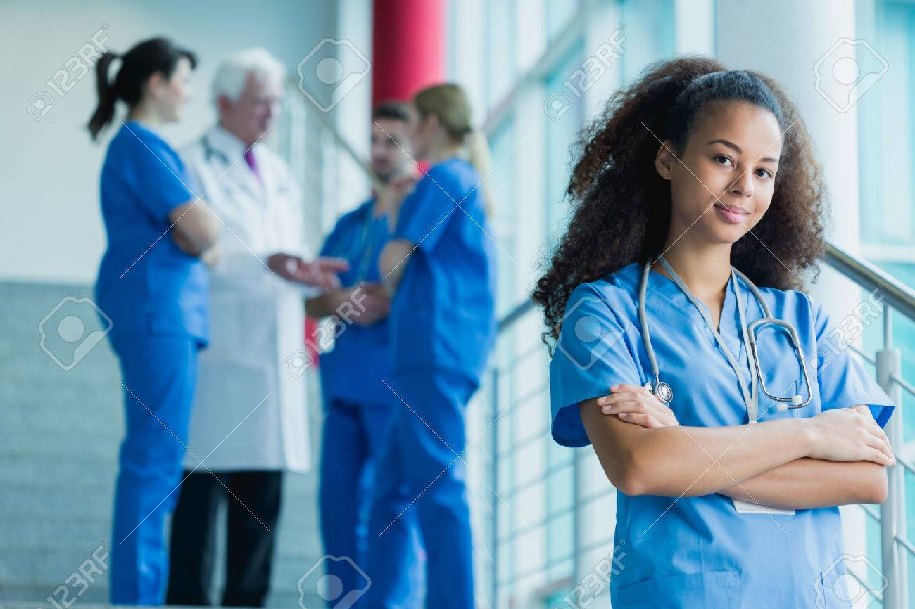 Afroamerican medical student standing on stairs, in the background group of students talking with a doctor - 57021386