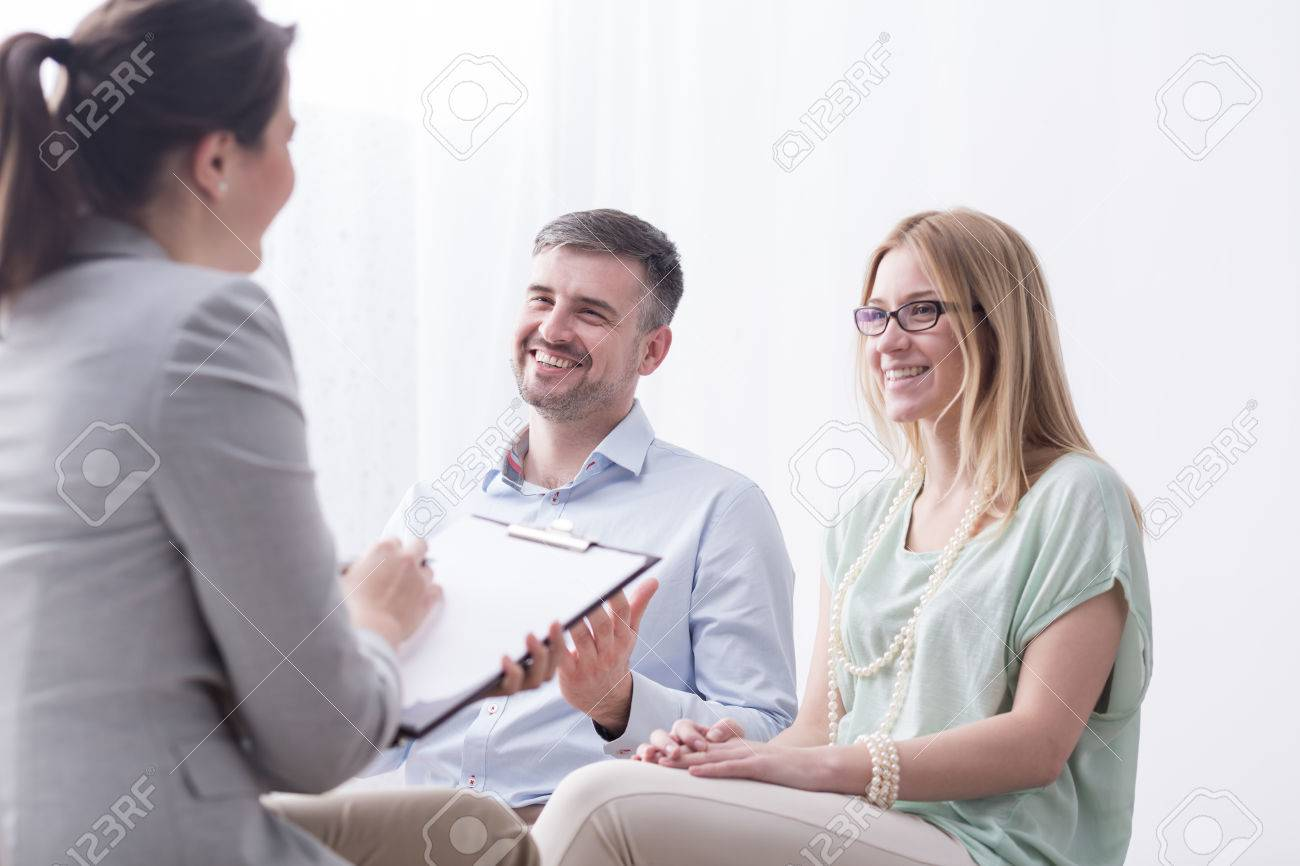 Psychotherapist filling in questionnaire on psychotherapy session with happy young marriage - 57022134