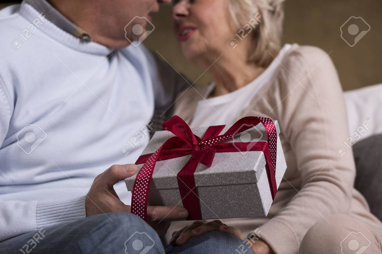 Older Woman Grateful To Her Husband For A Birthday Present In The First Plan Silver