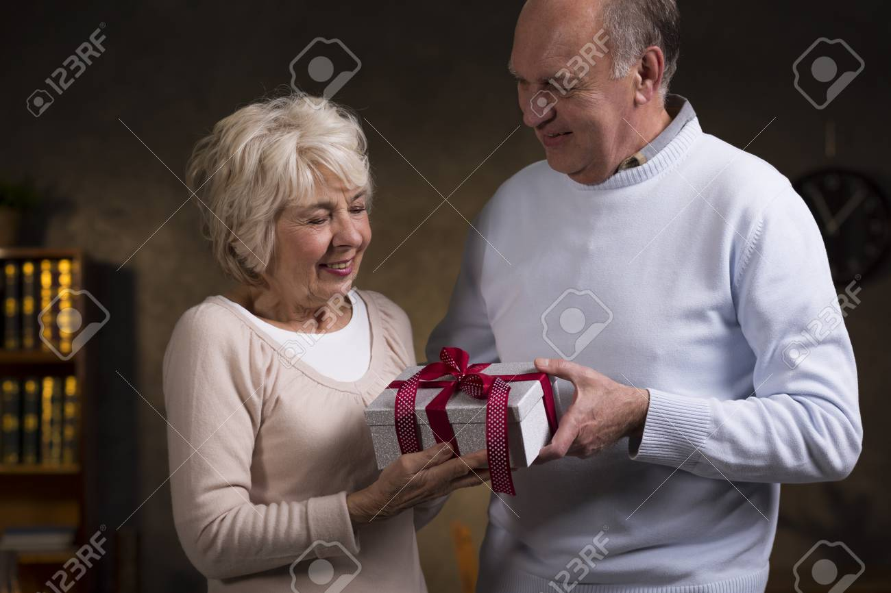 Happy Elderly Man And A Birthday Gift For Lovely Wife Giving Wifes Best Wishes