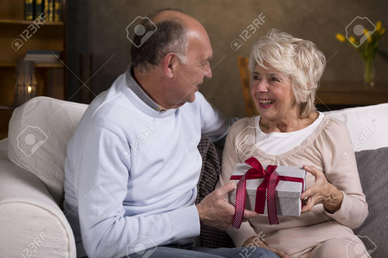 Loving Older Man Giving A Birthday Gift To His Happy Senior Wife Stock Photo
